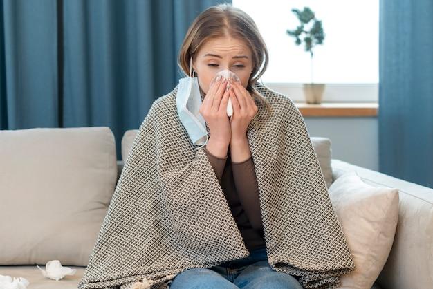 Молодая женщина в защитной стерильной медицинской маске в помещении