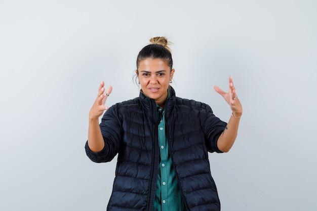 大きなサイズのサインを示し、陽気に見える、正面図のフグジャケットの若い女性。