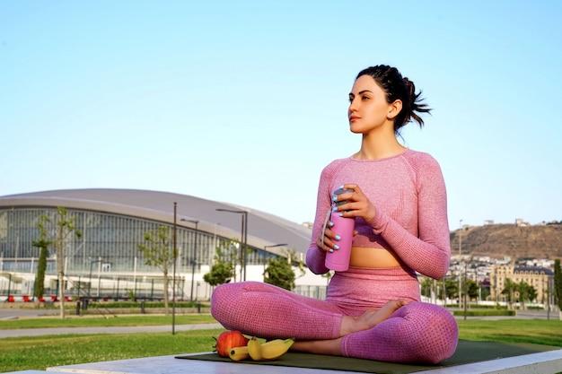 Молодая женщина в фиолетовой рубашке и брюках на траве днем в зеленом парке с розовой бутылкой