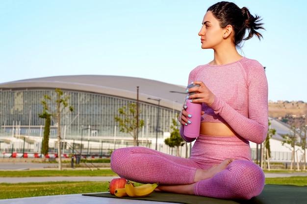 분홍색 셔츠를 들고 녹색 공원 안에 낮 동안 잔디에 보라색 셔츠와 바지에 젊은 여자