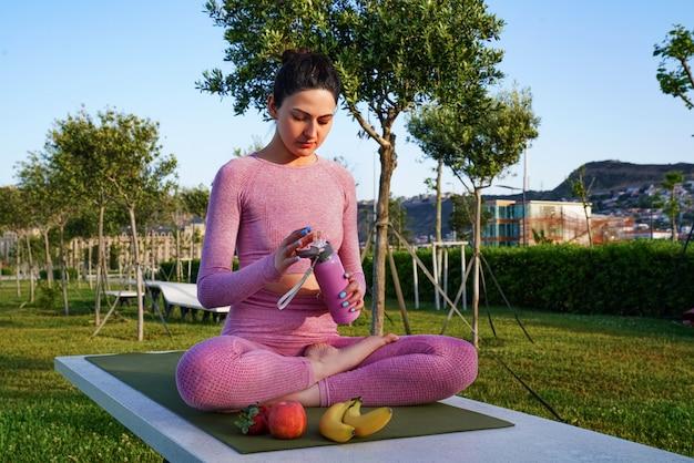 緑の公園の瞑想中の昼間の間に紫色のシャツとズボンの芝生の上の若い女性