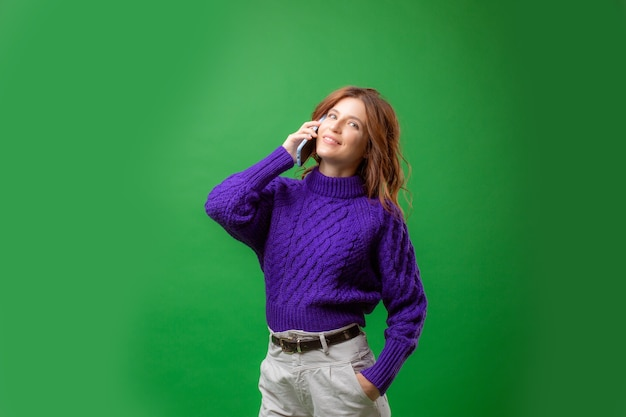 Молодая женщина в фиолетовом свитере разговаривает по мобильному телефону на зеленом фоне студии Premium Фотографии
