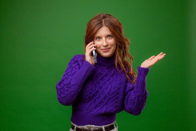 Молодая женщина в фиолетовом свитере разговаривает по мобильному телефону на зеленом фоне студии