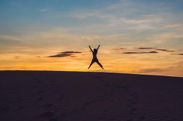 日没または夜明けにラジアン砂砂漠の若い女性