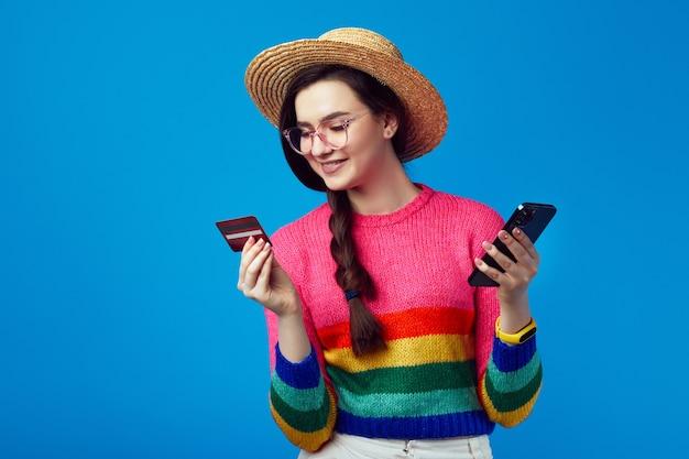 플라스틱 신용 카드와 휴대 전화를 들고 무지개 스웨터에 젊은 여자