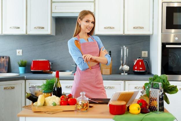 彼女の台所に立っている赤いエプロンの若い女性