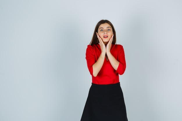 Молодая женщина в красной блузке, черной юбке держится руками за щеки и выглядит мило