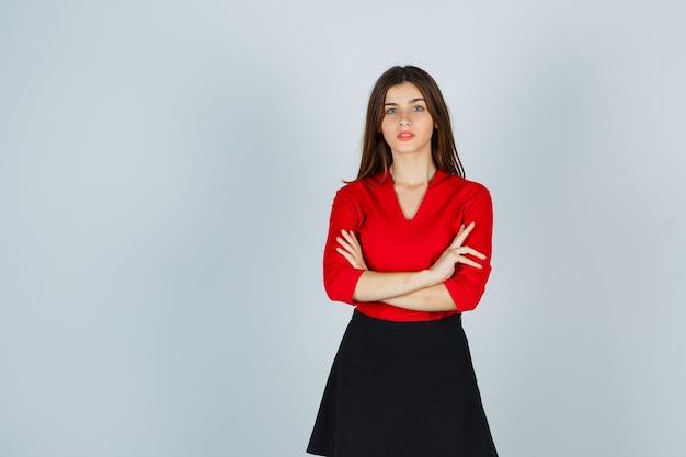 Молодая женщина в красной блузке, черной юбке стоит, скрестив руки, и выглядит уверенно