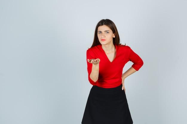 赤いブラウス、黒いスカートのストレッチの手で若い女性