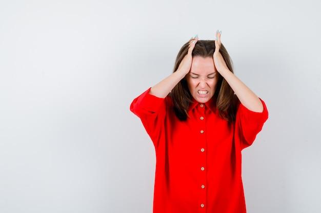 頭に手を置いてイライラしている赤いブラウスの若い女性、正面図。