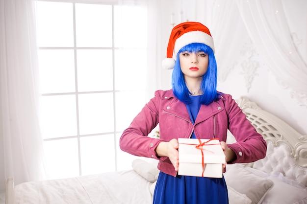 빨간 크리스마스 모자에있는 젊은 여자