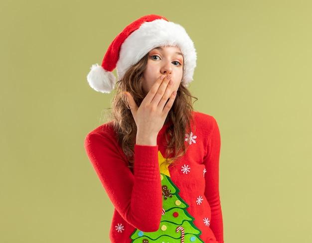 Молодая женщина в красном рождественском свитере и шляпе санта-клауса счастлива и позитивно дует воздушный поцелуй, стоя над зеленой стеной
