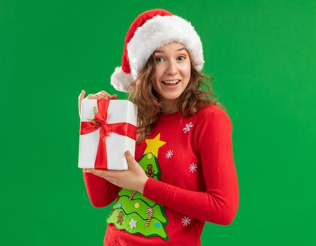 Молодая женщина в красном рождественском свитере и шляпе санта-клауса держит подарок, глядя в камеру со счастливым лицом, улыбаясь, стоя на зеленом фоне