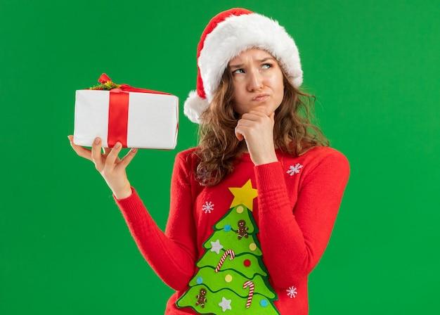 빨간 크리스마스 스웨터와 녹색 배경 위에 턱 생각 서에 손으로 올려 선물을 들고 산타 모자에 젊은 여자