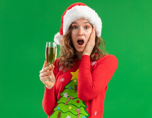 빨간 크리스마스 스웨터와 산타 모자에 젊은 여자는 녹색 배경 위에 서있는 그녀의 뺨에 손으로 놀란 카메라를보고 샴페인 잔을 들고