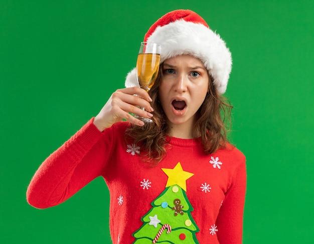 빨간 크리스마스 스웨터와 산타 모자에 젊은 여자가 카메라를보고 샴페인 잔을 들고 짜증과 녹색 배경 위에 서있는 짜증