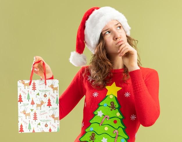 赤いクリスマスのセーターとサンタの帽子の若い女性は、緑の壁の上に立っている彼女のあごに手で考えて見上げるクリスマスプレゼントと紙袋を保持しています