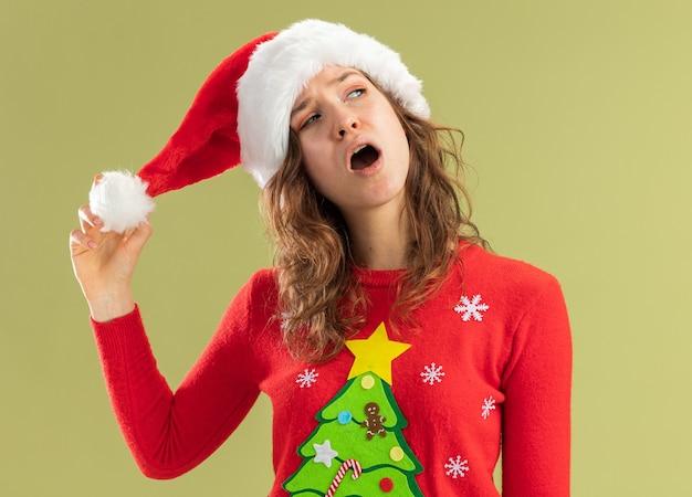 빨간 크리스마스 스웨터와 산타 모자에 젊은 여자는 녹색 벽 위에 의아해 서 찾고