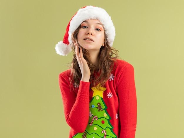 빨간 크리스마스 스웨터와 산타 모자에 젊은 여자는 녹색 벽 위에 서 의아해