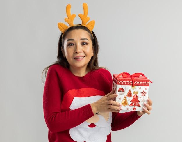 Молодая женщина в красном рождественском свитере в забавной оправе с оленьими рогами держит рождественский подарок, улыбается весело, счастливая и позитивная