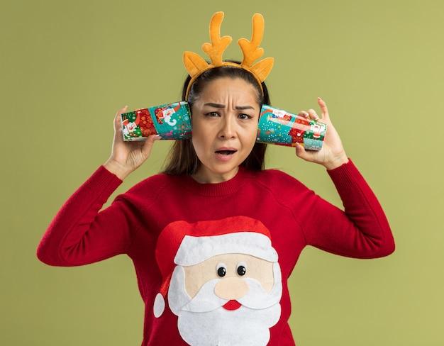 녹색 배경 위에 서 혼란 스 러 워 찾고 그녀의 귀에 다채로운 종이 컵을 들고 사슴 뿔 재미 테두리를 입고 빨간 크리스마스 스웨터에 젊은 여자