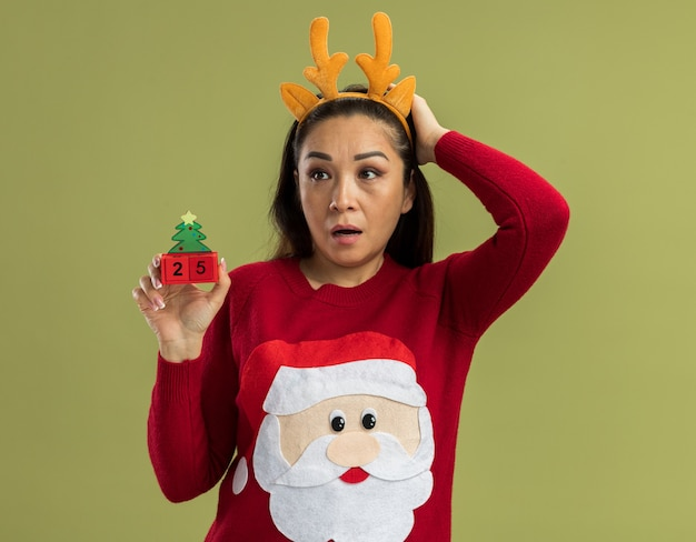 赤いクリスマスセーターの若い女性は、緑の壁の上に立って混乱し、心配して脇を見て、日付25のおもちゃの立方体を保持している鹿の角を持つ面白いリムを身に着けています