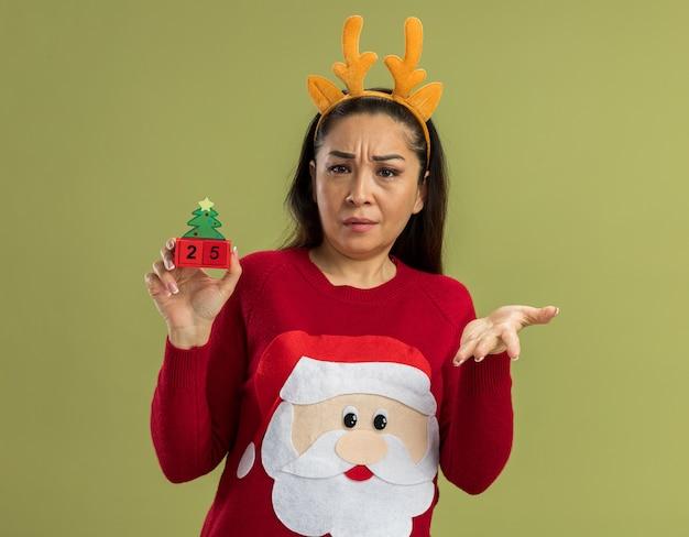 빨간 크리스마스 스웨터에 젊은 여자가 카메라를보고 혼란스러워 녹색 배경 위에 서있는 불만에 팔을 올리는 혼란 날짜 25 장난감 큐브를 들고 사슴 뿔을 가진 재미있는 테두리를 입고