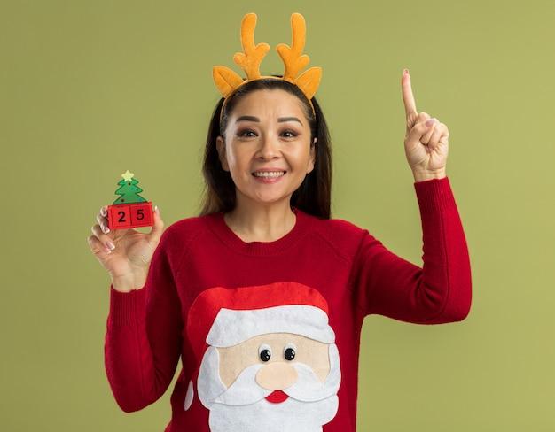 녹색 배경 위에 서 카메라 행복 하 고 쾌활 한 보여주는 검지 손가락을보고 날짜 25 장난감 큐브를 들고 사슴 뿔 재미 테두리를 입고 빨간 크리스마스 스웨터에 젊은 여자