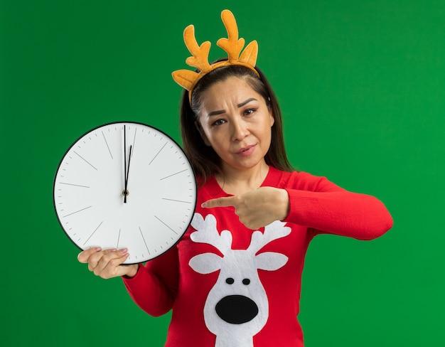 녹색 배경 위에 서 심각한 얼굴로 카메라를보고 검지 손가락으로 가리키는 벽 시계를 들고 사슴 뿔 재미 테두리를 입고 빨간 크리스마스 스웨터에 젊은 여자