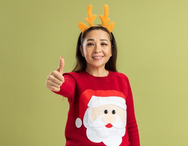행복하고 긍정적 인 엄지 손가락을 보여주는 웃 고보고 사슴 뿔 재미 테두리를 입고 빨간 크리스마스 스웨터에 젊은 여자