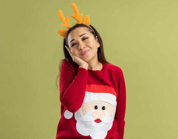 Молодая женщина в красном рождественском свитере в забавной оправе с оленьими рогами смотрит с улыбкой на лице счастливой и позитивной