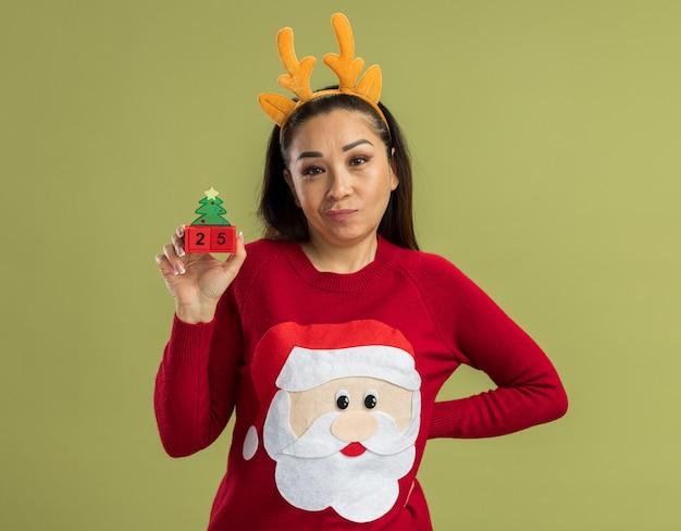 緑の壁の上に立っている懐疑的な笑顔で日付25のおもちゃの立方体を示す鹿の角と面白いリムを身に着けている赤いクリスマスセーターの若い女性