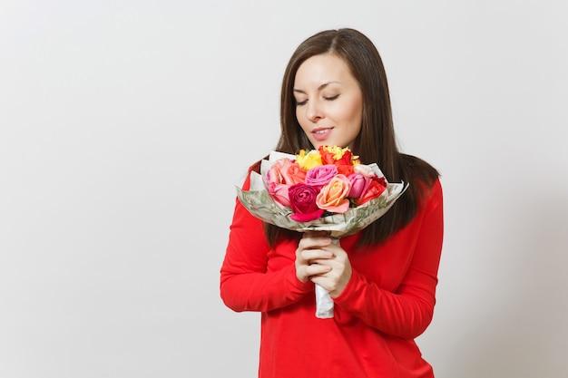 빨간 옷을 입은 젊은 여성이 흰색 배경에 격리된 아름다운 장미 꽃다발을 들고 킁킁거리고 있습니다. 광고 공간을 복사합니다. 성 발렌타인 데이 또는 국제 여성의 날 개념.