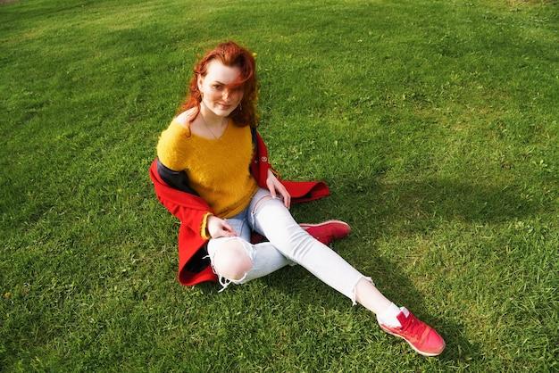 빨간 코트와 청바지에 젊은 여자는 봄 공원에서 푸른 잔디에 앉아