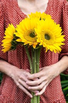ひまわりの大きな花束を保持している赤いドレスの若い女性。