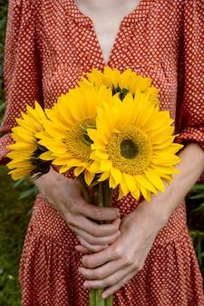 ひまわりの大きな花束を保持している赤いドレスの若い女性