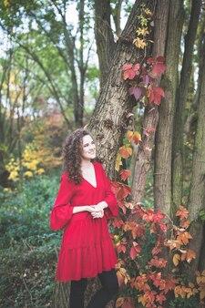 秋の公園で赤いドレスの若い女性