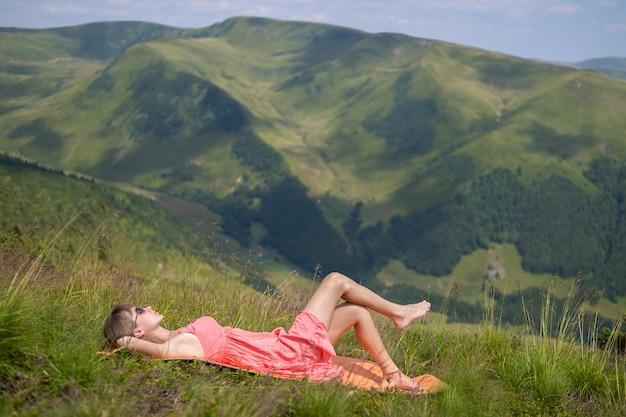 Молодая женщина в красном платье, лежа на зеленом травянистом лугу в теплый солнечный день в летних горах, наслаждаясь видом на природу.