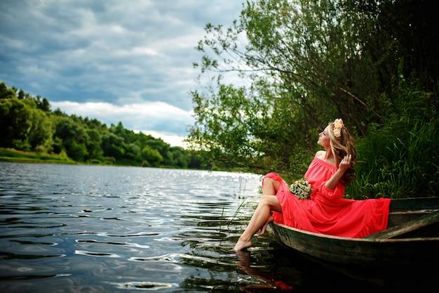 Молодая женщина в красном платье на лодке. на голове у девушки венок