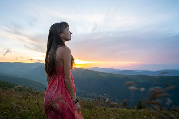 自然の景色を楽しむ秋の山々の風の強い夜に芝生のフィールドに立っている赤いドレスの若い女性。