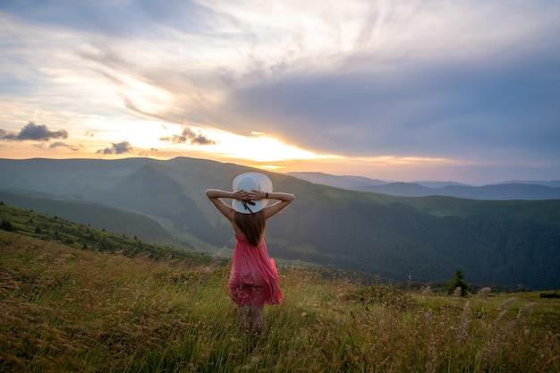 바람이 부는 저녁에 풀밭에 서 있는 빨간 드레스를 입은 젊은 여성이 자연의 전망을 즐기고 있습니다.