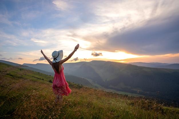 自然の景色を楽しみながら手を上げて秋の山の風の強い夜に芝生のフィールドに立っている赤いドレスの若い女性。