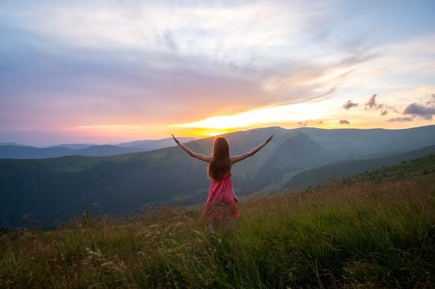 Молодая женщина в красном платье стоя на травянистом поле ветреным вечером в осенних горах, поднимая руки, наслаждаясь видом на природу.