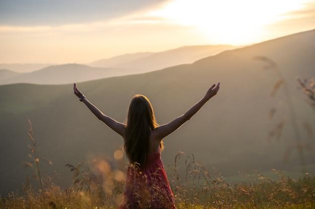 自然の景色を楽しみながら手を上げて秋の山々の風の強い夜に草が茂った牧草地に立っている赤いドレスの若い女性。