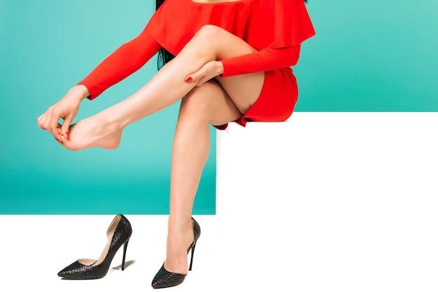 Молодая женщина в красном платье страдает от боли в ноге в офисе из-за неудобной обуви