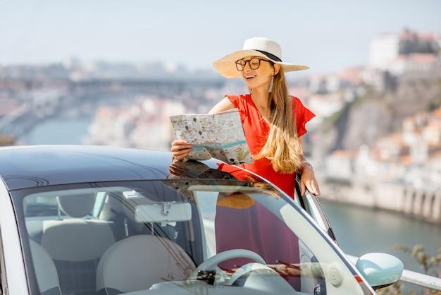 ポルト市、ポルトガルで車で旅行赤いドレスの若い女性