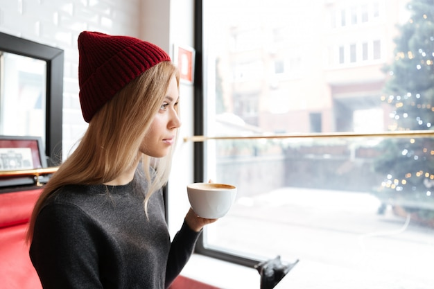 Молодая женщина в красной шляпе, пить кофе у окна