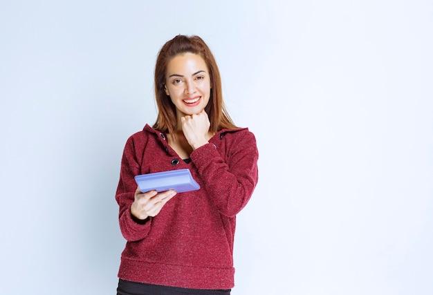 青い上着を着た若い女性が青い電卓で何かを計算し、最終結果を示す