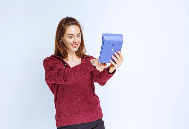 파란색 계산기에서 무언가를 계산하는 빨간 재킷을 입은 젊은 여성