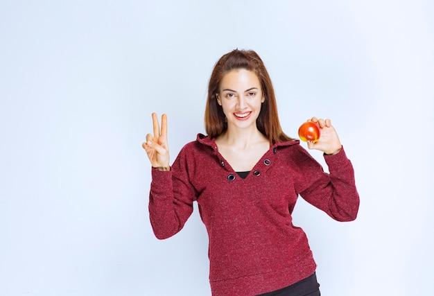 빨간 사과를 들고 긍정적인 손 기호를 보여주는 빨간 재킷에 젊은 여자